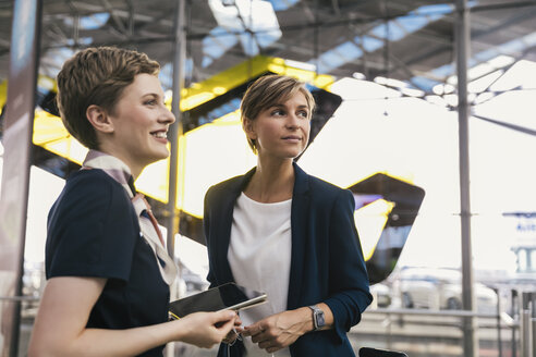 Smiling airline employee with tablet and businesswoman at the airport - MFF04771