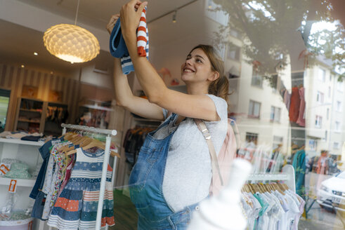 Smiling pregnant woman shopping for baby clothing in a boutique - KNSF05425