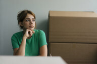 Thoughtful woman next to cardboard boxes in office - KNSF05434