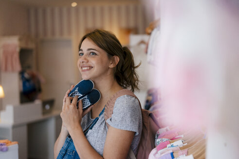 Smiling pregnant woman shopping for baby clothing in a boutique - KNSF05440