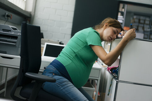 Exhausted pregnant woman sitting at desk in office - KNSF05443