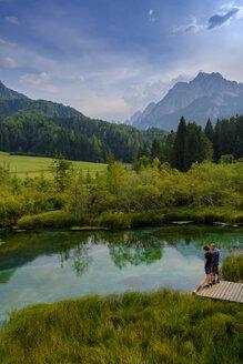 Slovenia, Gorenjska, near Ratece, Lake Zelenci, father and son on jetty - LBF02308