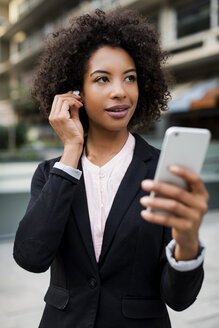 Portrait of smiling usinesswoman with smartphone putting on earphones - MAUF01984