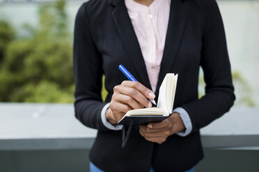 Hand of businesswoman taking notes outdoors, close-up - MAUF01993