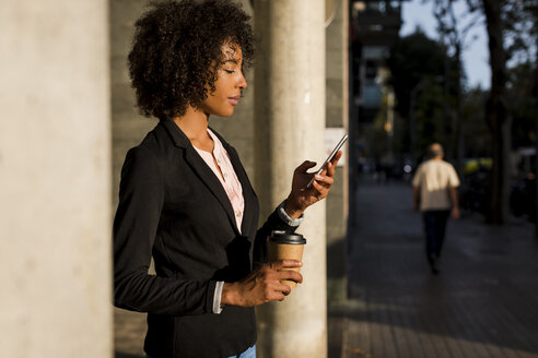 Businesswoman with coffee to go looking at cell phone at evening twilight - MAUF01999