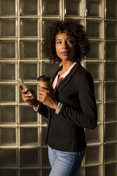 Portrait of businesswoman with coffee to go and cell phone at evening twilight - MAUF02002