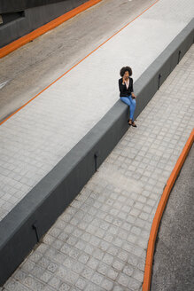 Businesswoman on the phone sitting on wall - MAUF02008