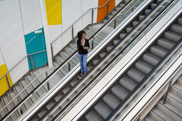 Businesswoman on the phone standing on escalator - MAUF02011