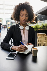 Portrait of businesswoman taking notes at pavement cafe - MAUF02014