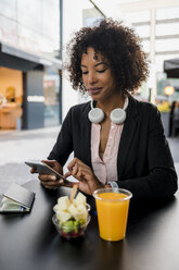 Portrait of businesswoman using cell phone at pavement cafe - MAUF02020