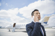 Businessman talking on cell phone on tarmac - HEROF01944