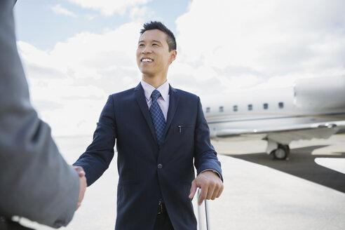 Businessmen handshaking  on tarmac with corporate jet - HEROF01950