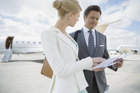 Business people reviewing paperwork on tarmac - HEROF01956
