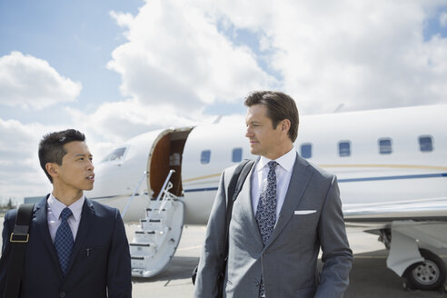Businessmen on tarmac with corporate jet - HEROF01962