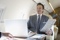 Businessman with newspaper laughing on corporate jet - HEROF01977
