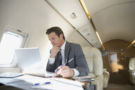 Businessman with laptop working on corporate jet - HEROF01983