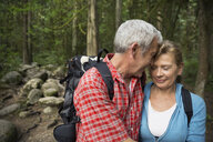 Couple hugging on hiking trail in woods - HEROF02022