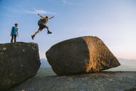 Man jumping across boulders, Pitchoff Mountain, Adirondack Mountains, New York State, USA - AURF07950