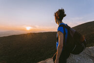 Female hiker looking at view of sunset, Pitchoff Mountain, Adirondack Mountains, New York State, USA - AURF07953