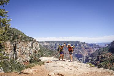 Hikers high fiving in Grand Canyon, Arizona, USA - AURF07989