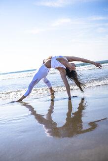 Woman doing yoga on beach - AURF08004