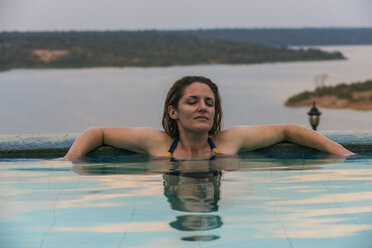 Africa, Uganda, Queen Elizabeth National Park, Woman relaxing in a pool above Kazinga channel - RUNF00510