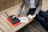 Close-up of businessman sitting on a bench using laptop and diary - MAUF02025