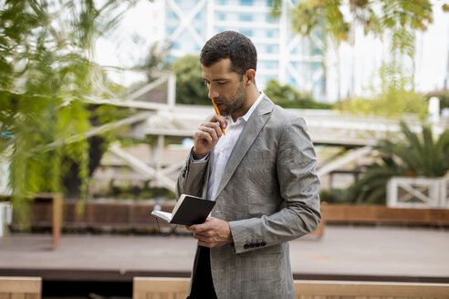 Businessman standing outdoors looking into notebook - MAUF02031