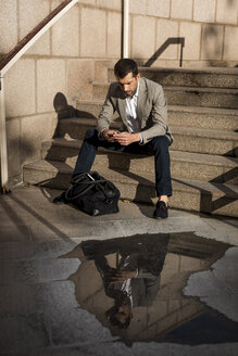 Businessman with bag sitting on stairs using cell phone - MAUF02034