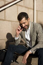 Smiling businessman with bag sitting on stairs talking on cell phone - MAUF02037