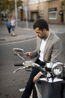 Businessman on motorscooter checking cell phone - MAUF02040
