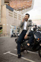 Smiling businessman on motorscooter talking on cell phone - MAUF02043