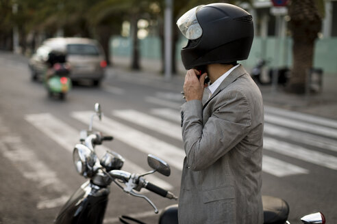 Businessman next to motorscooter putting on helmet - MAUF02046