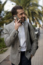 Happy businessman in the city talking on cell phone - MAUF02049