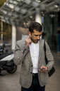 Businessman with cell phone and bluetooth earbuds in the city - MAUF02052