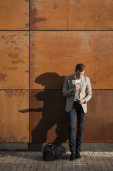 Businessman standing at a wall writing into notebook - MAUF02055