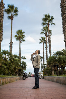 Happy businessman talking on cell phone on promenade with palm trees - MAUF02064
