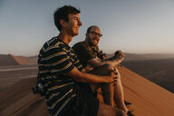 Namibia, Namib desert, Namib-Naukluft National Park, Sossusvlei, two smiling men sitting on Dune 45 at sunrise - LHPF00240