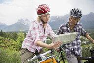 Couple on mountain bikes reading map on hillside - HEROF02060