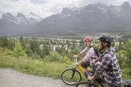 Couple riding mountain bikes on hillside - HEROF02069