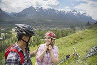 Couple with mountain bikes on hillside - HEROF02072