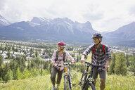 Couple walking with mountain bikes on hillside - HEROF02075