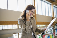 Businesswoman talking on cell phone in office lobby - HEROF02255