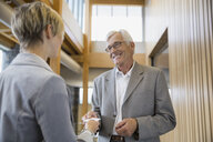 Business people exchanging business cards in office lobby - HEROF02270