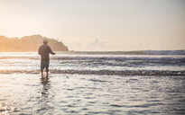 Rear view shot of a man standing at the beach at sunset - INGF11335