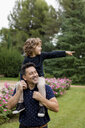 Happy father carrying son on shoulders in park - MAUF02076