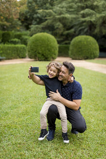 Happy father and son on taking a selfie in park - MAUF02082