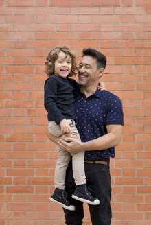 Happy father carrying son at brick wall - MAUF02091