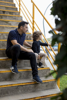 Father and son sitting on stairs in the city - MAUF02097