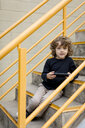 Portrait of boy sitting on stairs with handheld game console - MAUF02100